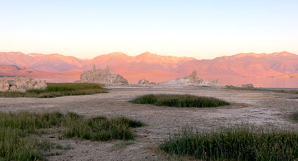 The eastern shore of Mono Lake at sunrise. The Sierra Nevada glows with light while the large tufas are in shade. Patches of marsh grass dot the foreground.
