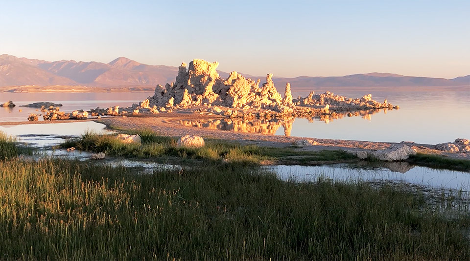 Sunrise lighting up a large irregular tufa in the water with the Sierra Nevada mountains as a backdrop.