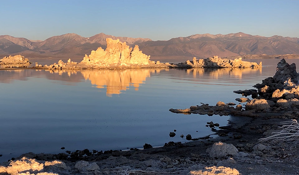 A large tufa reflecting golden light into the water with the sunlit mountains of the Sierras in the background.