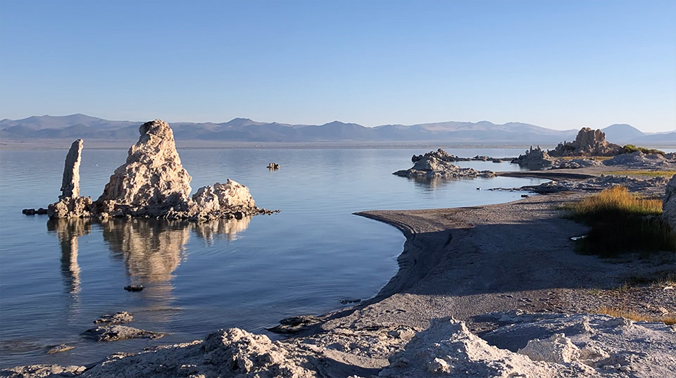 The long shadows right after sunrise etch the eastern shore as it gives way the lake itself. To the left, an ornate tufa is surrounded by the waters of Mono Lake.