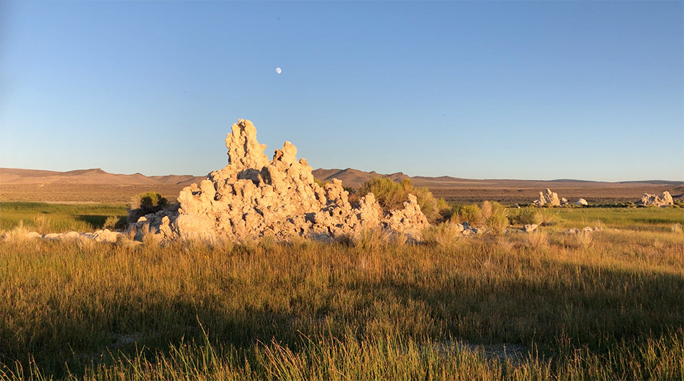 Marshland with islands of tufa, separating the eastern Mono Lake coastline from the surrounding desert. A full moon dominates the sky.